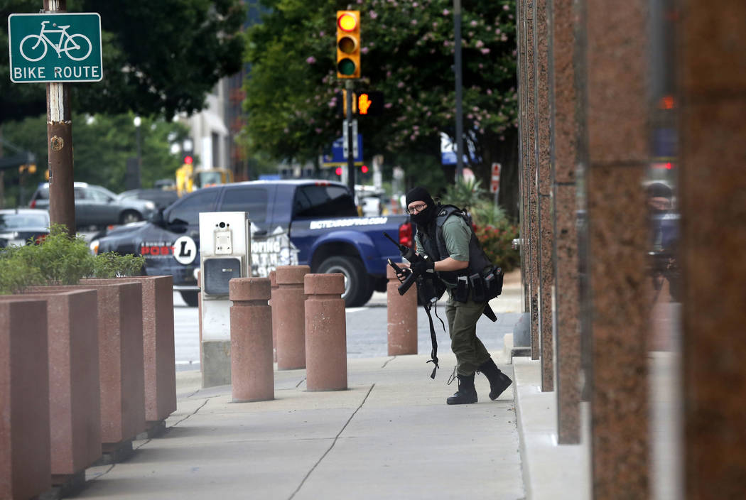 An armed shooter stands near the Earle Cabell Federal Building Monday, June 17, 2019, in downto ...