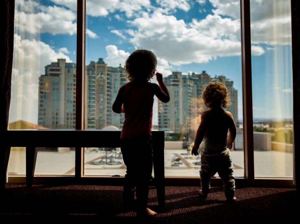 Dixie Baalman, 2, left, and Davey Baalman, 1, runs round their family's hotel room at the Sunco ...
