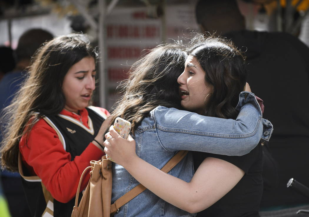 Friends embrace after shots were fired during the Toronto Raptors NBA basketball championship p ...