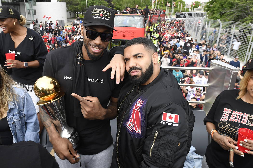 Toronto Raptors forward Kawhi Leonard points at his playoffs MVP trophy as he poses with perfor ...