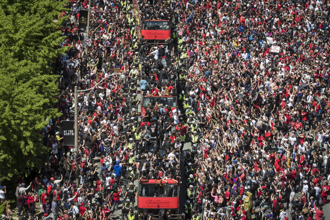 Members of the Toronto Raptors NBA basketball championship team ride on buses during a victory ...