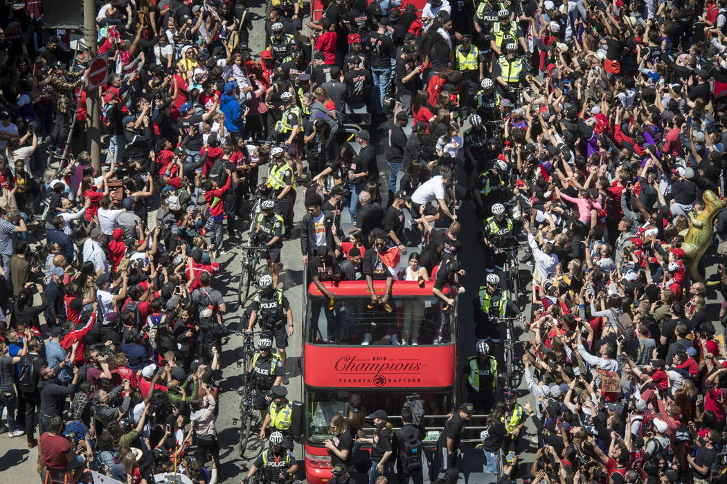 Members of the Toronto Raptors NBA basketball championship team ride on a bus during a victory ...