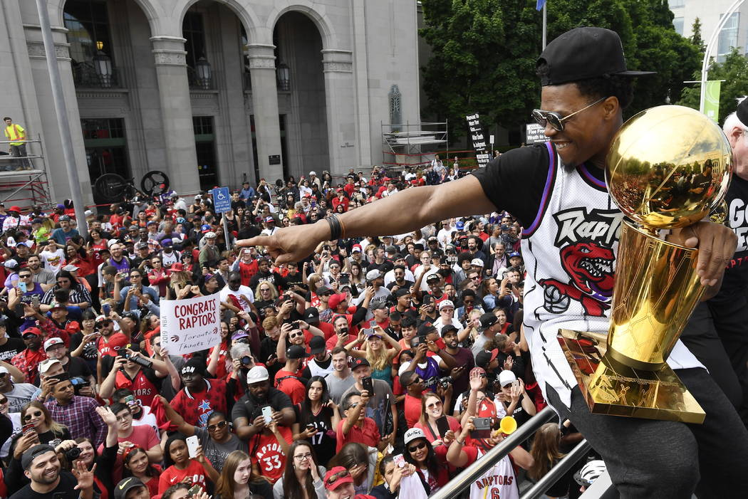 Toronto Raptors guard Kyle Lowry gestures towards fans while holding the Larry O'Brien Champion ...