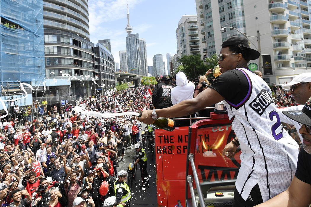 Toronto Raptors guard Kyle Lowry sprays champagne towards fans during the NBA basketball champi ...