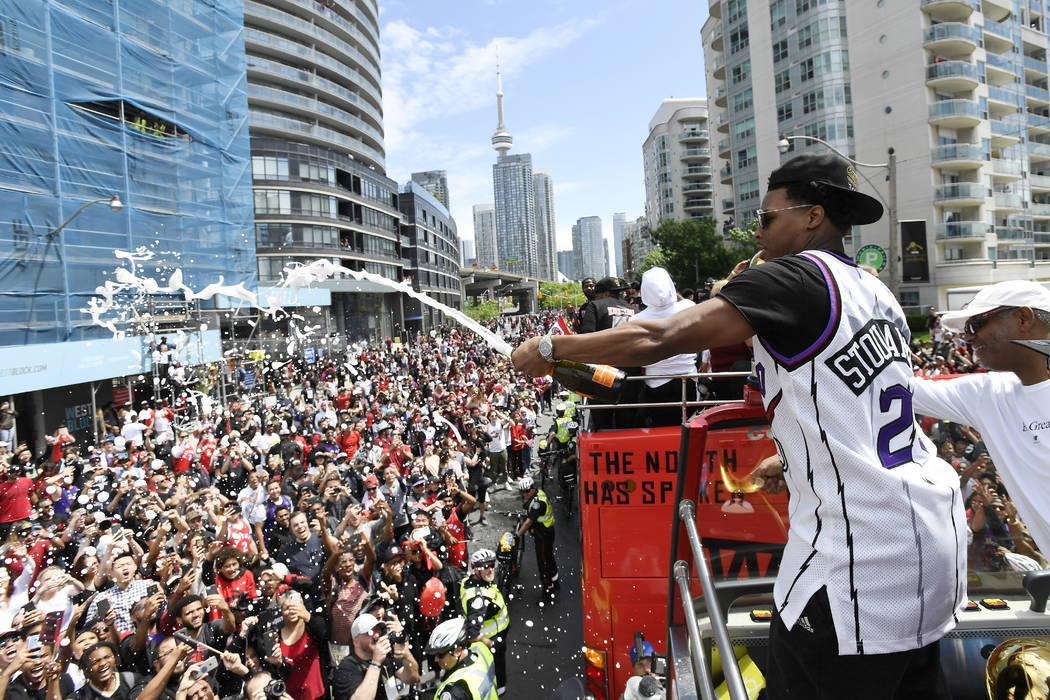 Toronto Raptors guard Kyle Lowry sprays champagne on fans during the NBA basketball championshi ...