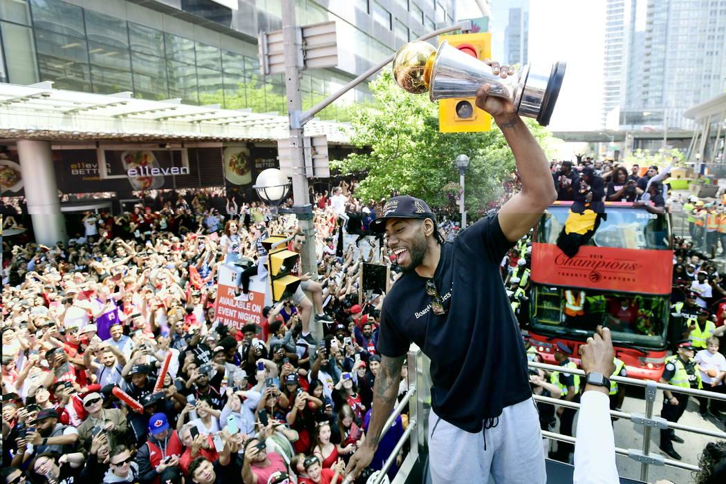 Toronto Raptors forward Kawhi Leonard hoists his playoffs MVP trophy during the NBA basketball ...