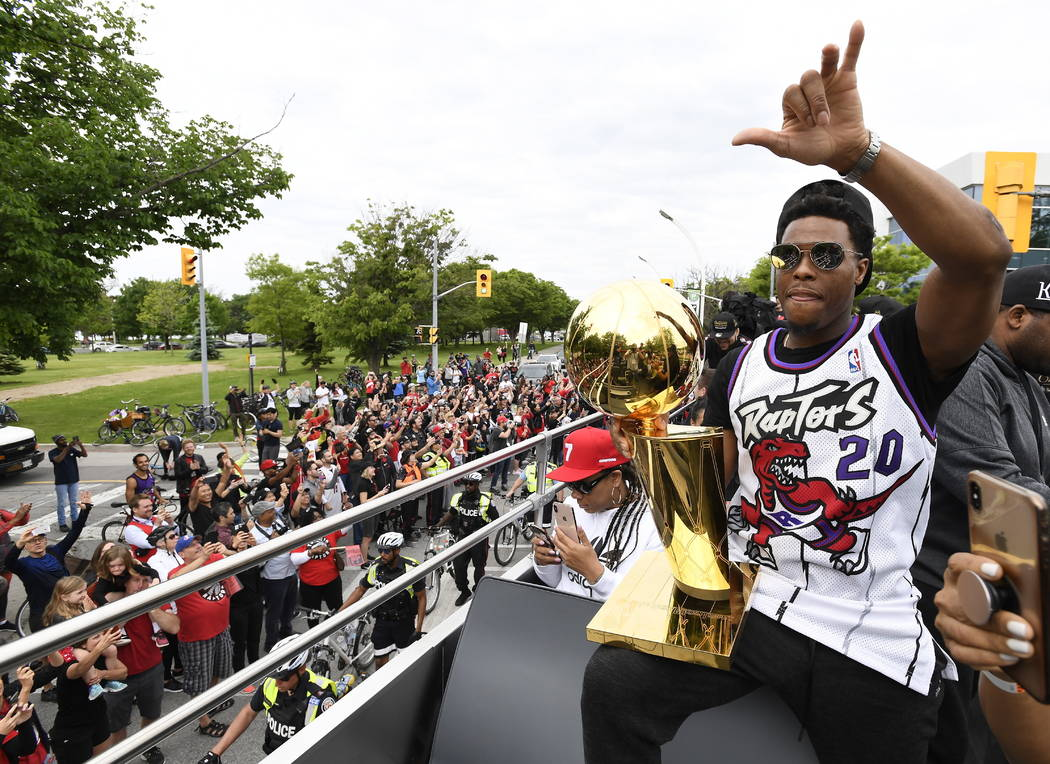 Toronto Raptors guard Kyle Lowry waves to fans while holding the Larry O'Brien Championship Tro ...