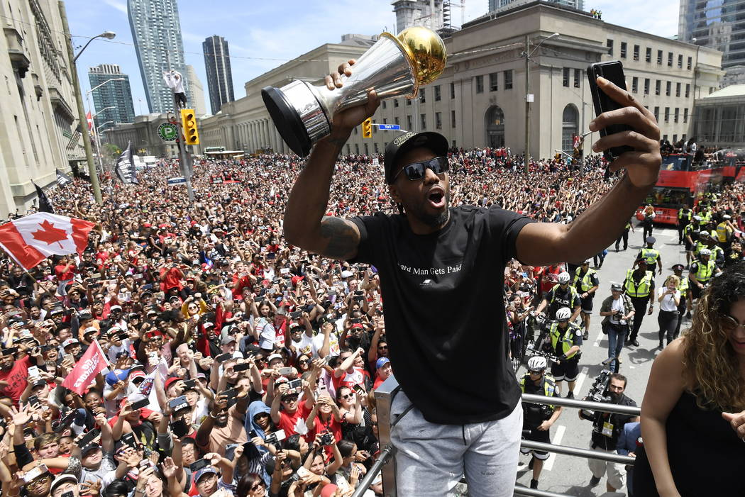 Toronto Raptors forward Kawhi Leonard takes a selfie holding his playoffs MVP trophy during the ...