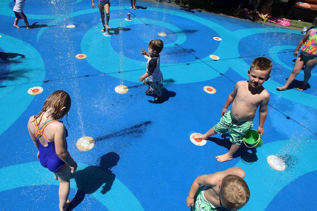 Children play at a splash pad at The District in Henderson on Friday, June 12, 2019. (Bizuayehu ...