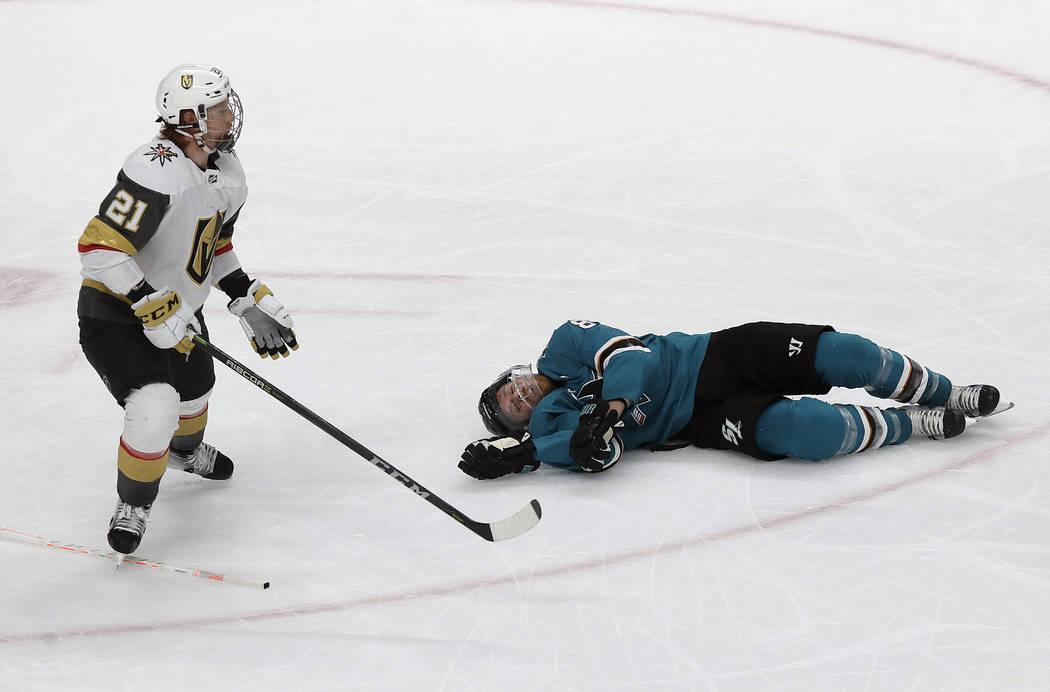 San Jose Sharks center Joe Pavelski, right, lies on the ice next to Vegas Golden Knights center ...