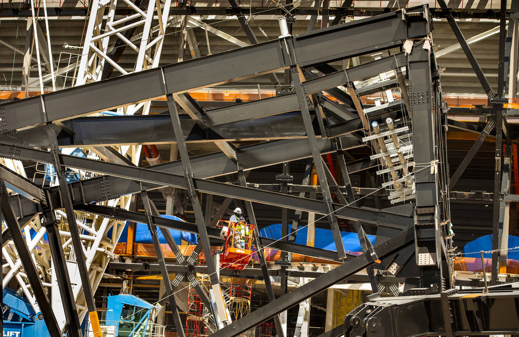 A crew in a lift examine a truss on the ground at Raiders Stadium where one of the 65-ton steel ...