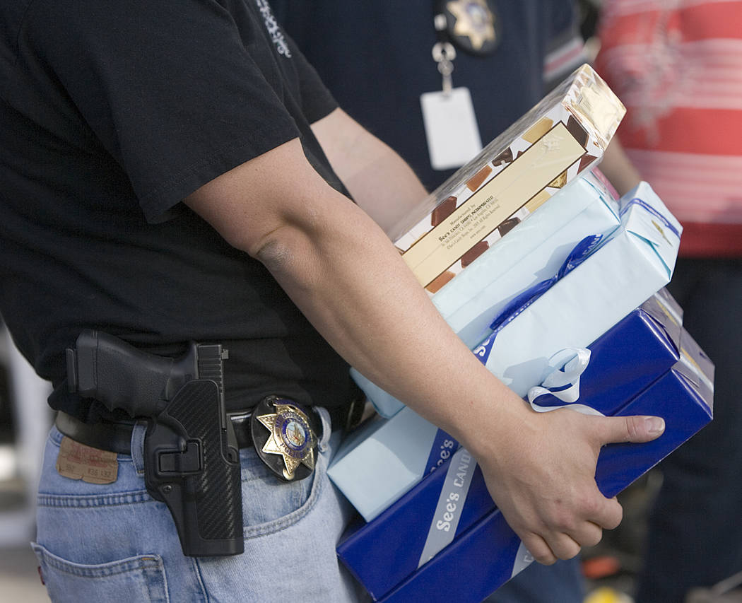 Las Vegas police carry boxes of See's Candy recovered at a residence at 1504 Cutler Drive, near ...