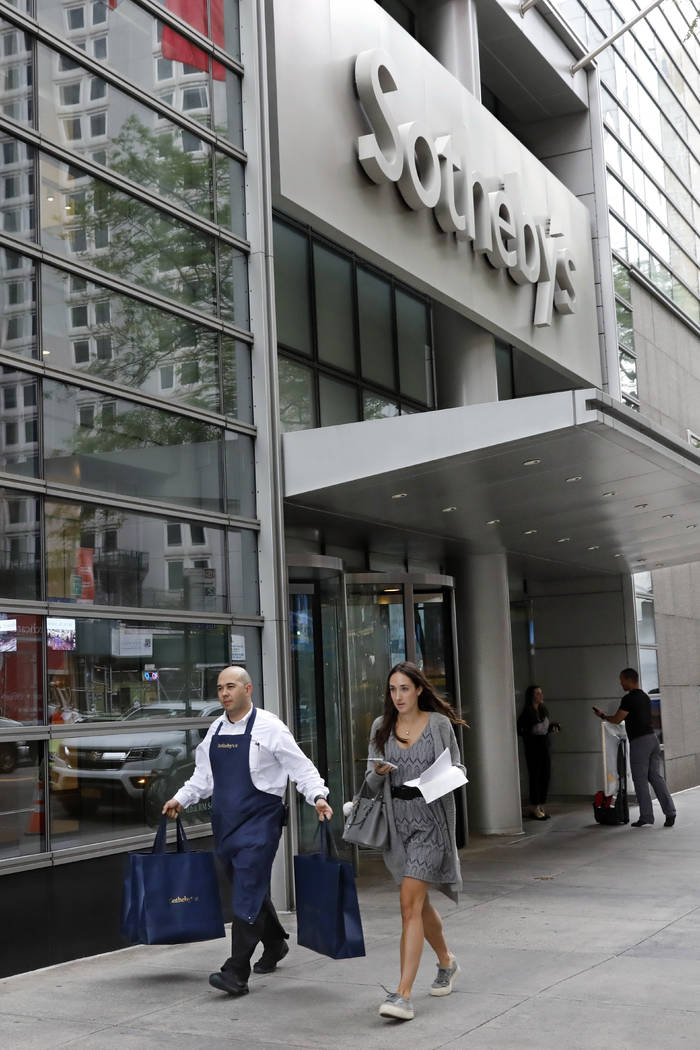 A Sotheby's worker carries bags outside the auction house, in New York, Monday, June 17, 2019. ...