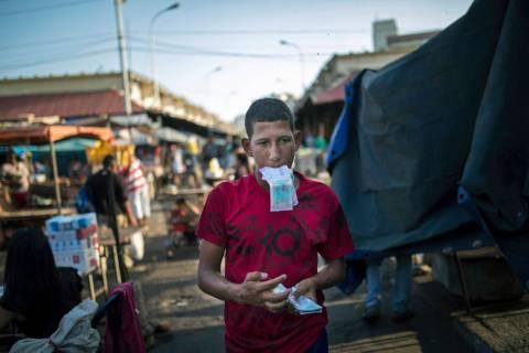 A flea market vendor counts his Bolivar bills in Maracaibo, Venezuela, May 16, 2019. Maracaibo ...