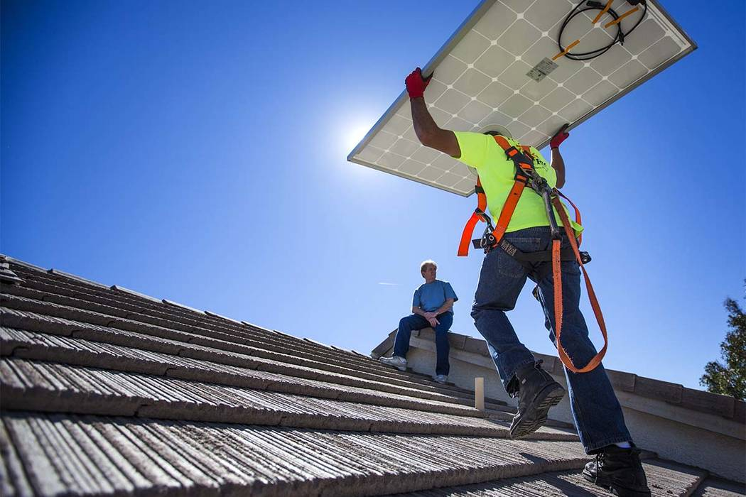 Matt Neifeld with Robco Electric carries a solar panel at a home in northwest Las Vegas on Frid ...