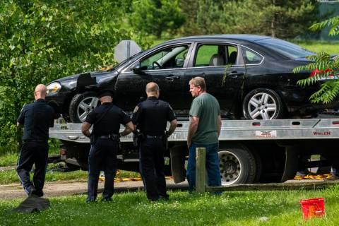 Police remove a black sedan from the Kalamazoo River near Verburg Park, Tuesday morning, June 1 ...