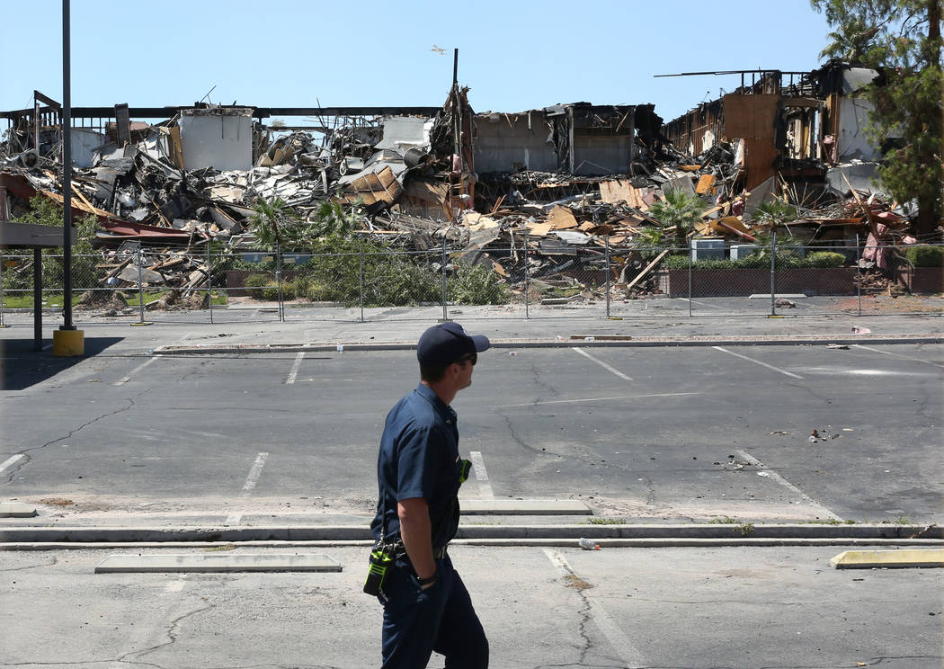 A Clark County firefighter walks past the rubble of burned-out office building at The Park at 3 ...