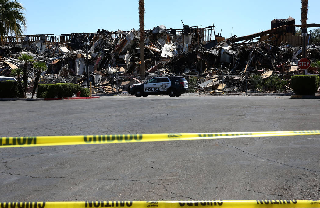 The rubble of burned-out office building at The Park at 3900 Paradise Road is blocked by cautio ...