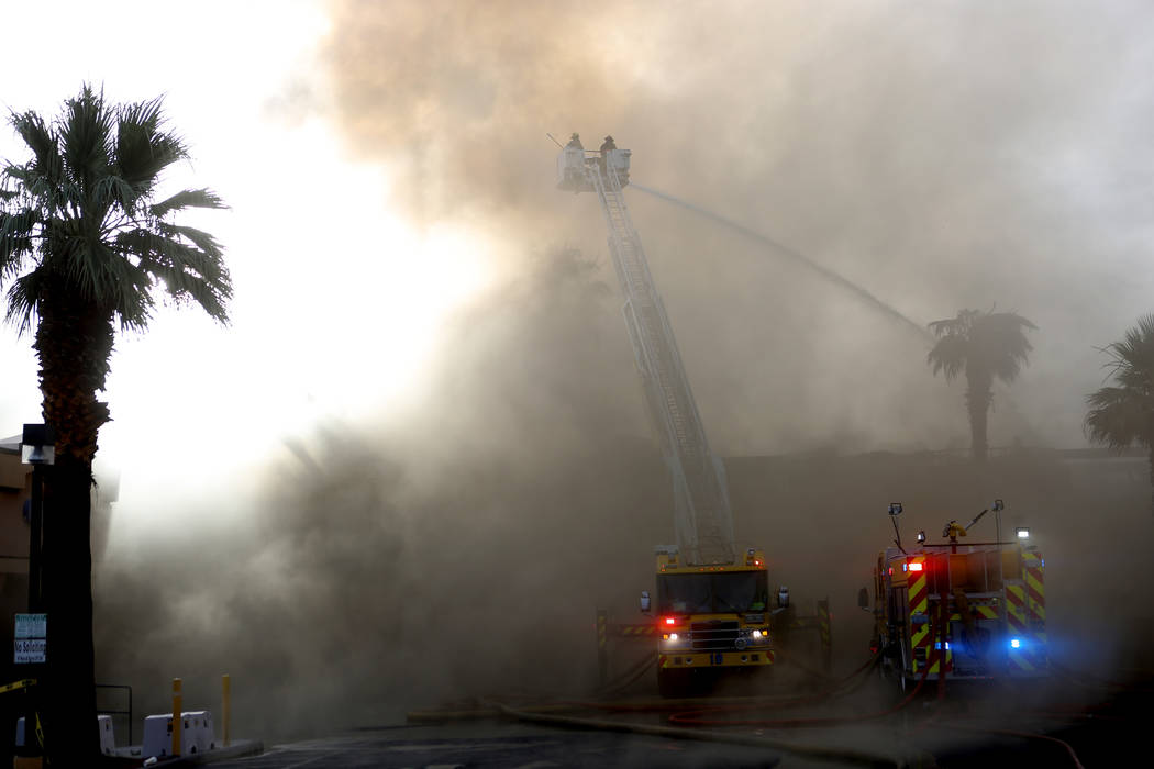 Firefighters work to gain control of a fire at aq business complex near Paradise Road and East ...