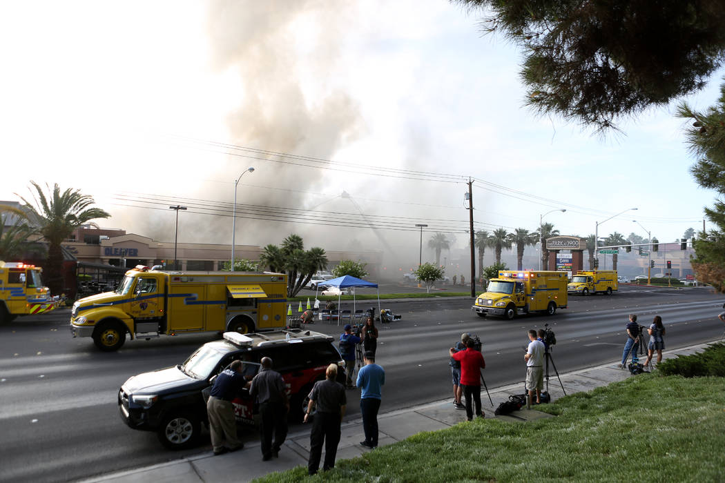 News media gather across the street from a business complex fire near Paradise Road and East Tw ...