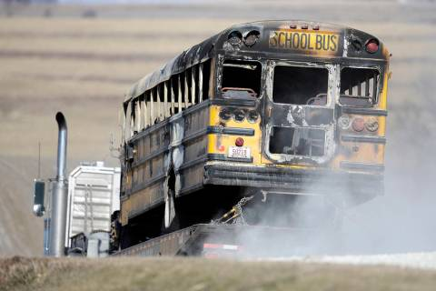 A burned school bus is transported by trailer near Oakland, Iowa, Tuesday, Dec. 12, 2017. A fir ...