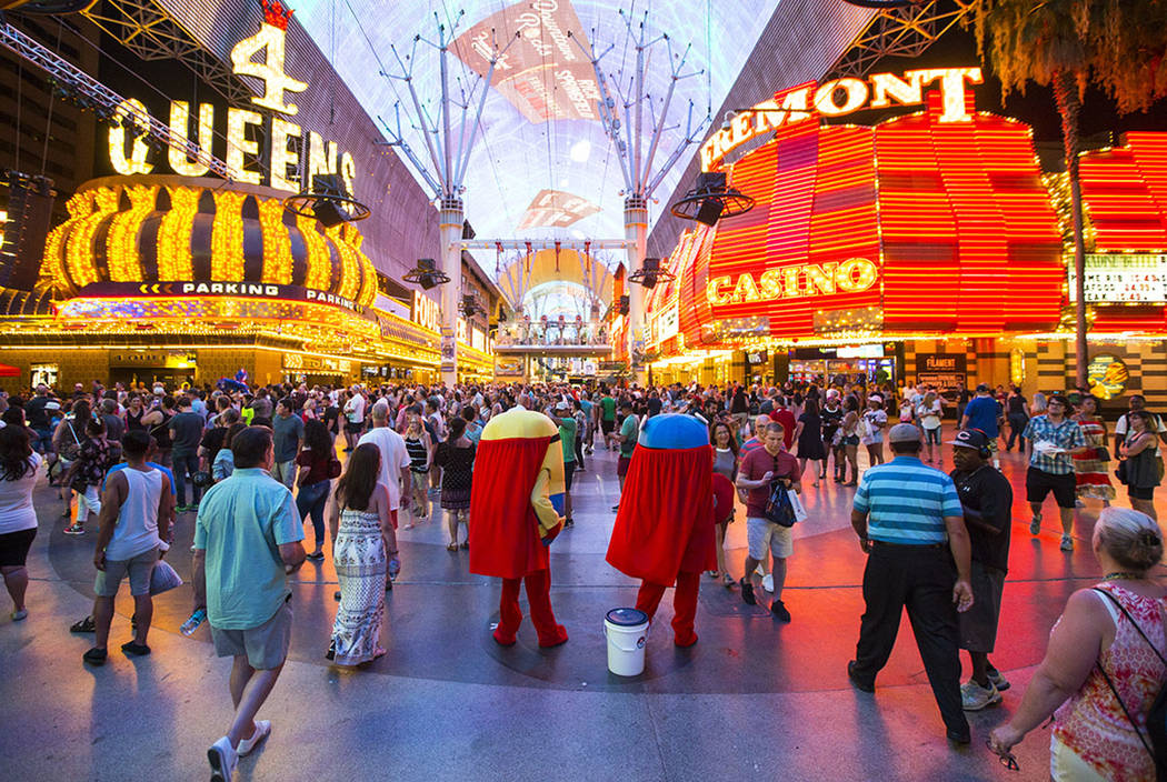 Buskers wait to pose with tourists for tips along the Fremont Street Experience in downtown Las ...