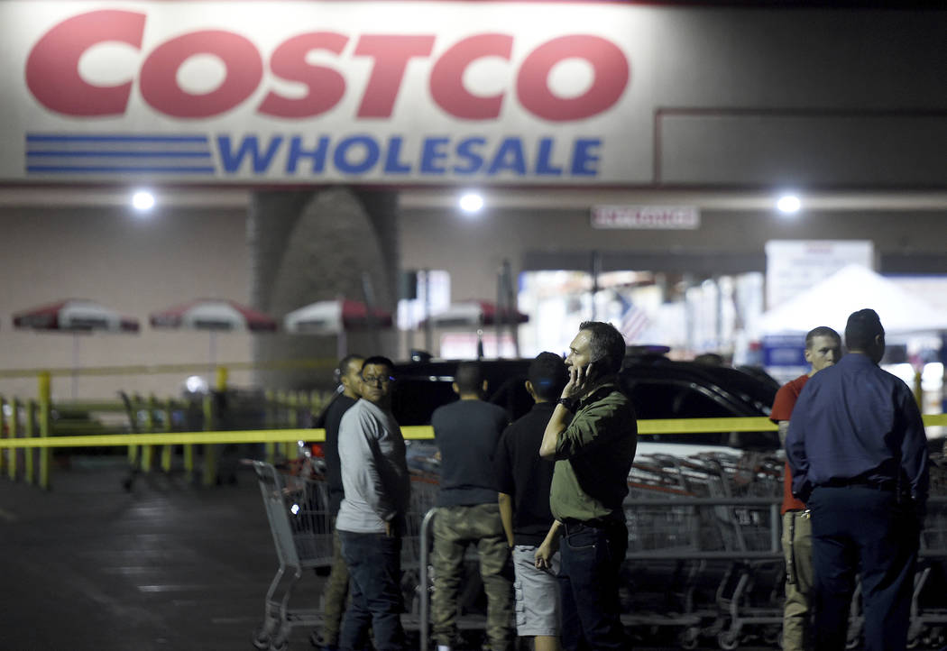 A Costco employee talks on the phone following a shooting within the wholesale outlet in Corona ...
