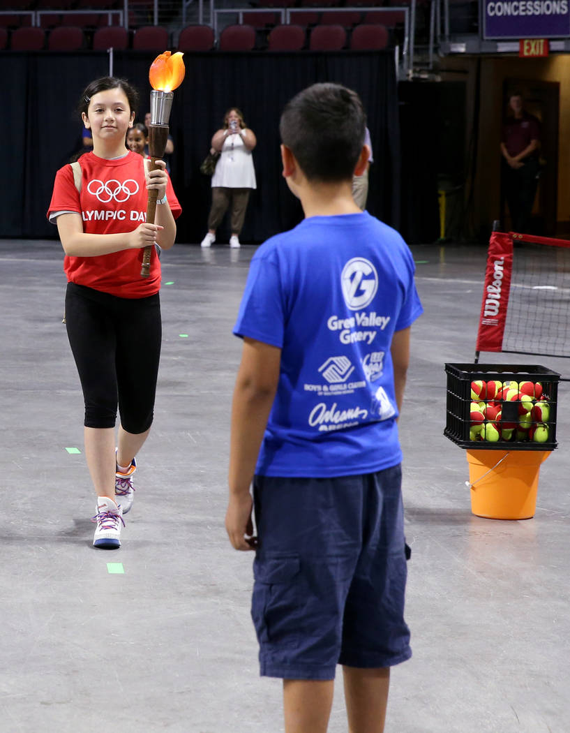 Bianca Perez, 11, of Lied Boys & Girls Club prepares to pass the torch to Brandon Paz, 10, ...