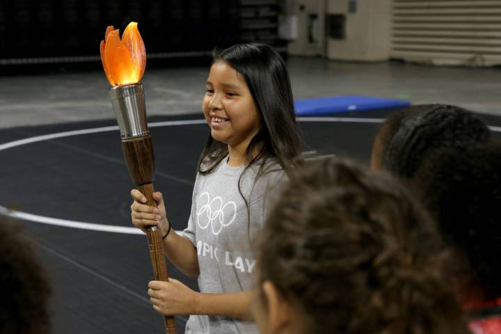 Destiny Chee, 11, carries the torch on Olympic Day at The Orleans in Las Vegas Tuesday, June 18 ...