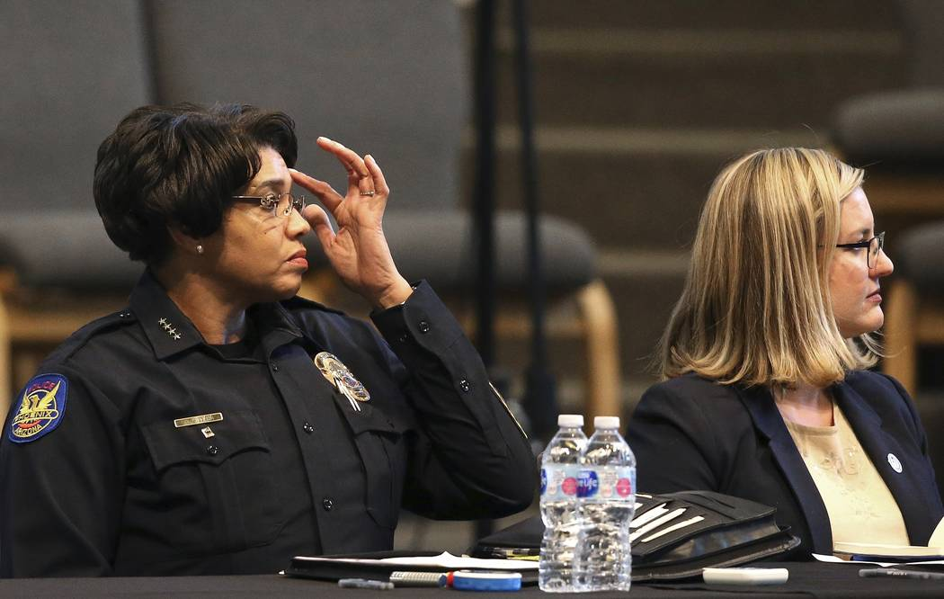 Phoenix Police Chief Jeri Williams, left, and Mayor Kate Gallego, right, listen to a speaker at ...