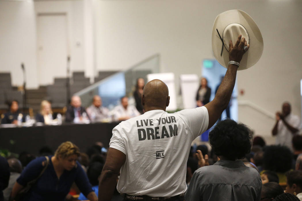 A Phoenix resident stands up to wave his cowboy hat in support of a speaker at a community meet ...