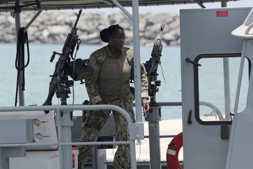 A U.S. Navy personnel prepares at a patrol boat to carry journalists to see damaged oil tankers ...