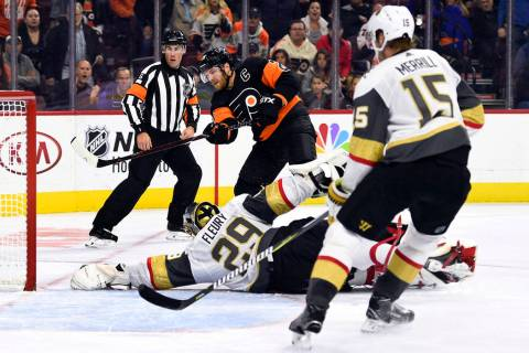 Philadelphia Flyers' Claude Giroux, center, watches the puck as Vegas Golden Knights' goaltende ...