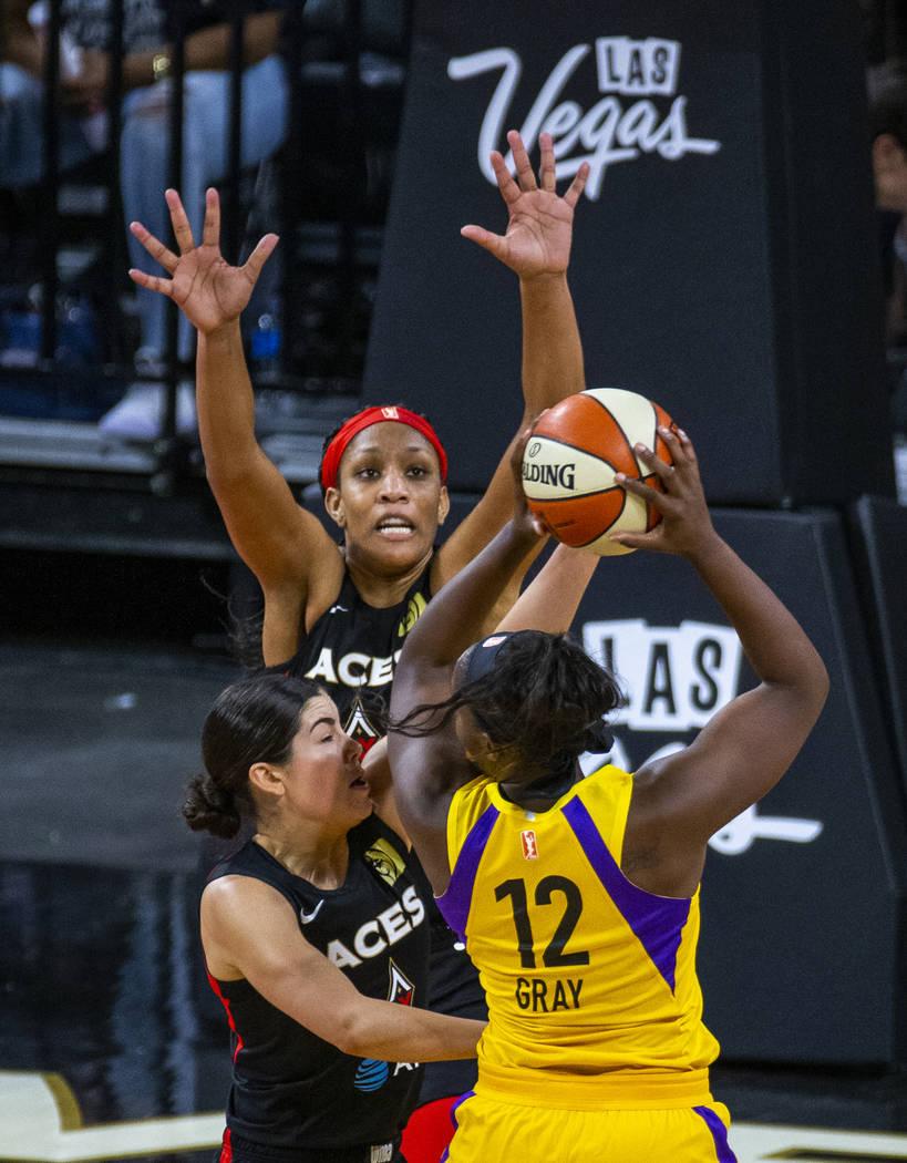 Las Vegas Aces center A'ja Wilson (22), center, and guard Kelsey Plum, left, defend the basket ...