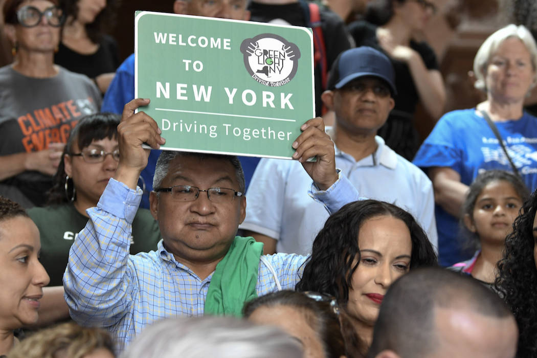 A man holds a sign as members of the state Assembly speak in favor of legislation of the Green ...