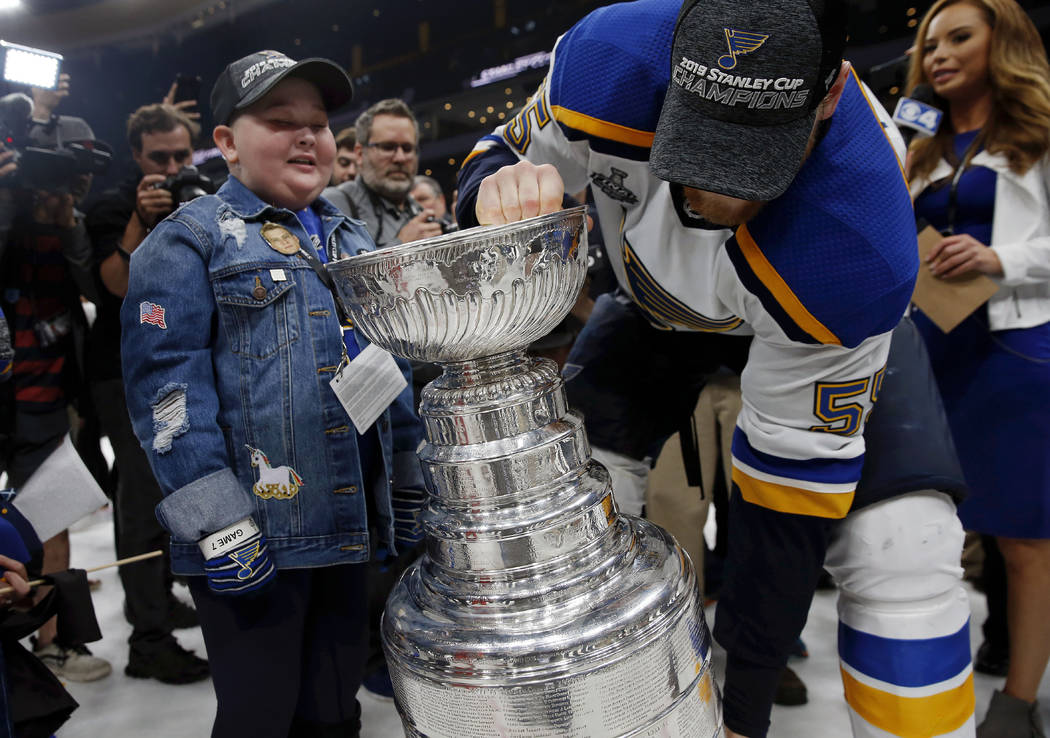 St. Louis Blues fan Laila Anderson, left, watches Colton Parayko lift the Stanley Cup while the ...