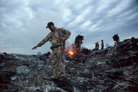 FILE - In this July 17, 2014 file photo, people walk amongst the debris at the crash site of a ...
