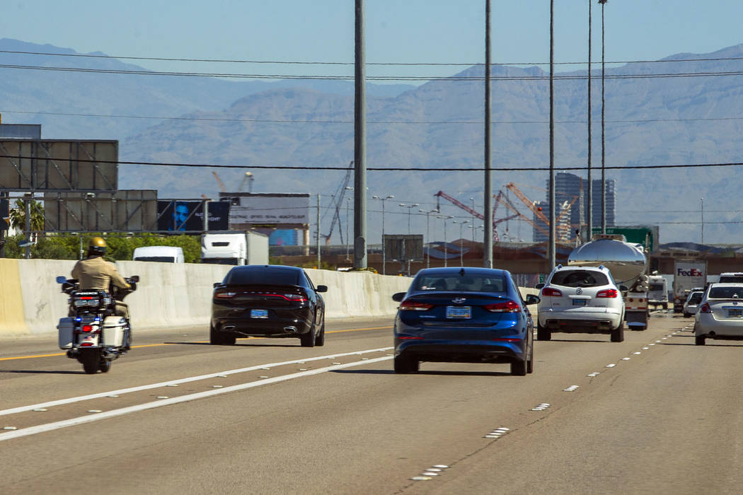 A Las Vegas Metropolitan motorcycle officer trails a vehicle in the HOV lane northbound on Inte ...