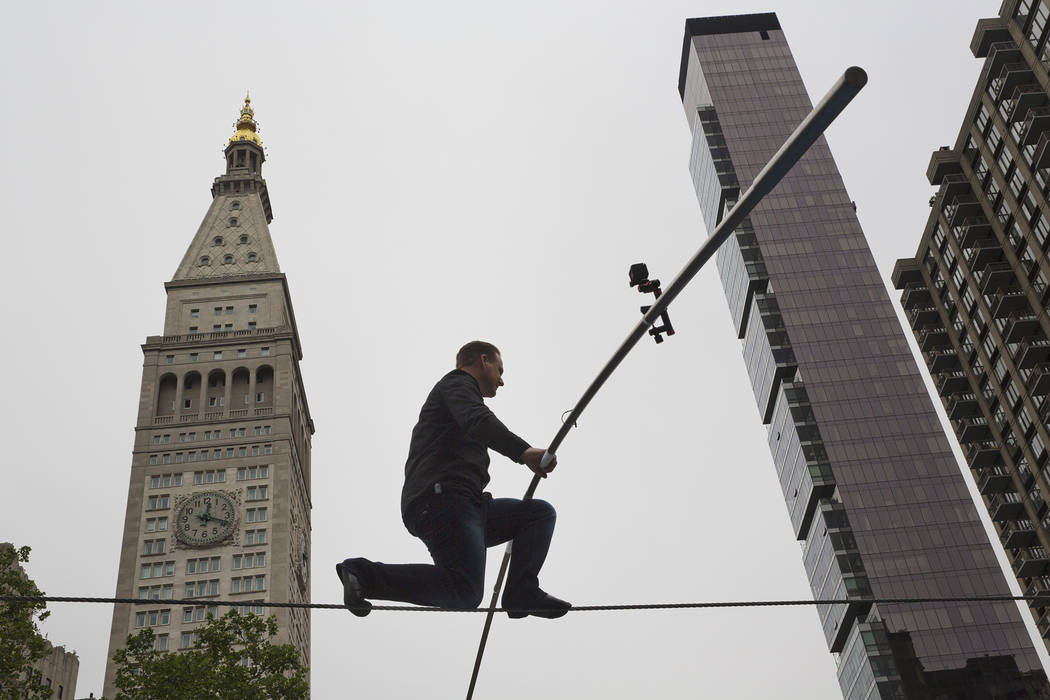 High-Wire Artist Nik Wallenda is famed by the Met Life building as he walks a tight rope, in ho ...