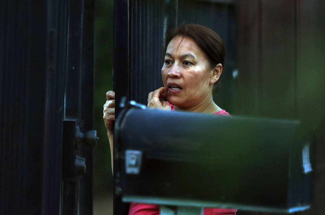 A woman watches as law enforcement officers surround a home where a gunman has taken refuge aft ...