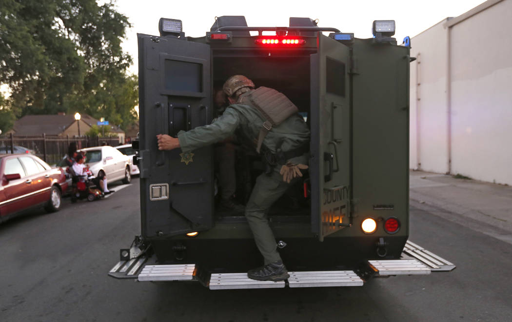 A law enforcement officer climbs into a tactical vehicle during a standoff with an armed suspec ...