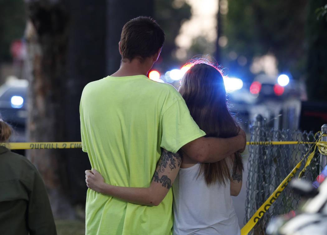 A man and woman watch as law enforcement officers surround a home where a gunman has taken refu ...