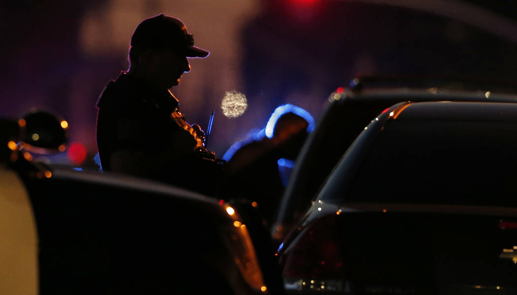 A law enforcement officer mans a barricade near a home that authorities have surrounded where a ...