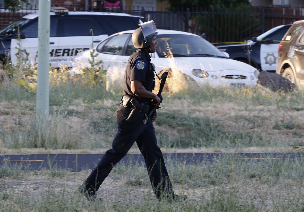 A Sacramento Police officer responds to the shooting of a fellow officer in Sacramento, Calif., ...