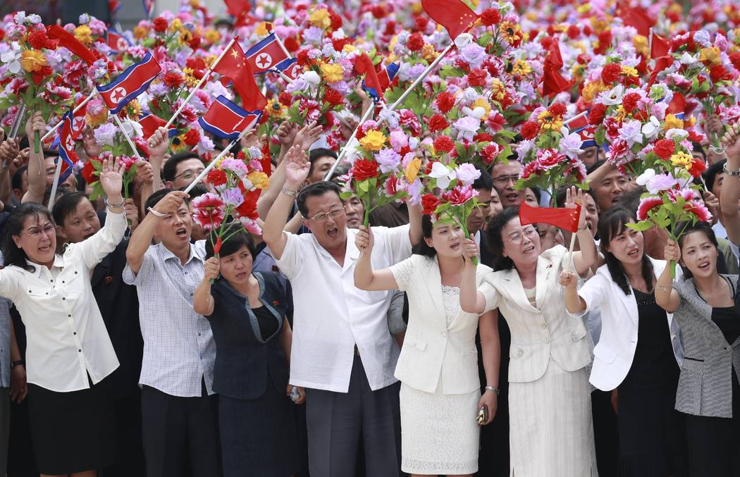 In this photo provided by China's Xinhua News Agency, people welcome Chinese President Xi Jinpi ...