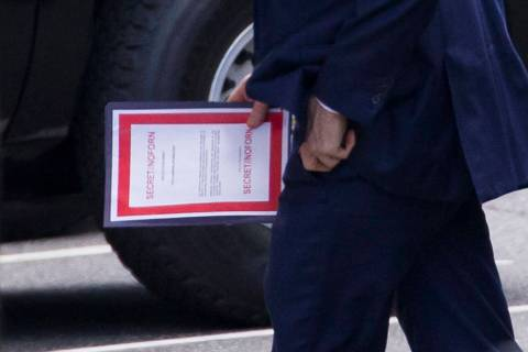 Outgoing acting Defense Secretary Patrick Shanahan carries a document labeled secret as he arri ...