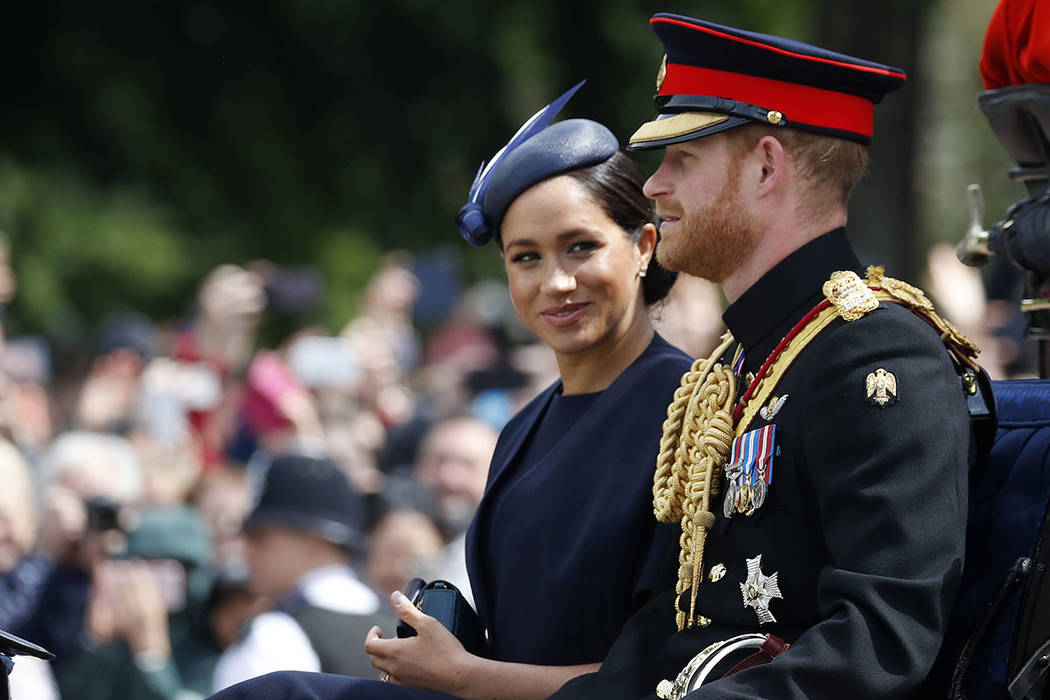 Britain's Meghan, the Duchess of Sussex and Prince Harry ride in a carriage to attend the annua ...