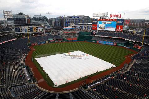A tarp covers the infield during a rain delay before a baseball game between the Philadelphia P ...