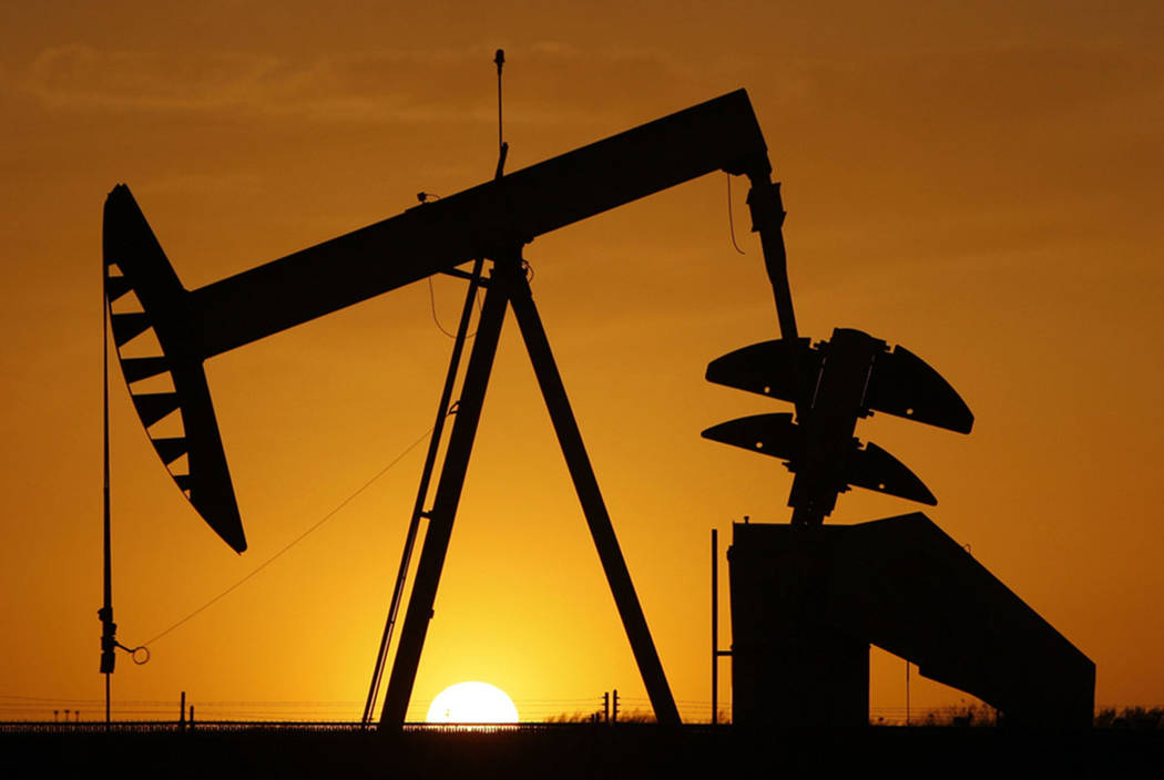 A pumpjack is silhouetted against the setting sun in Oklahoma City in 2012. (AP Photo/Sue Ogro ...