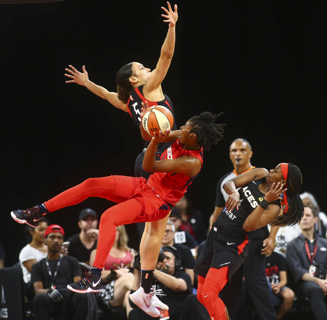 Washington Mystics guard Ariel Atkins (7) gets tripped up while going to the basket between Las ...
